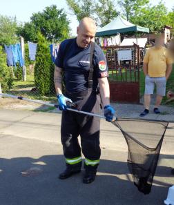 Egy tűzoltó merítőszákot tart, amiben egy fekete kiscica van