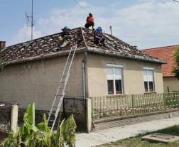 Önkéntes tűzoltók segítenek az ideiglenes helyreállítási munkákban a viharkárt szenvedett Sellye településen