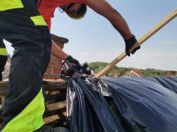 Önkéntes tűzoltó segít az ideiglenes helyreállítási munkákban a viharkárt szenvedett Sellye településen